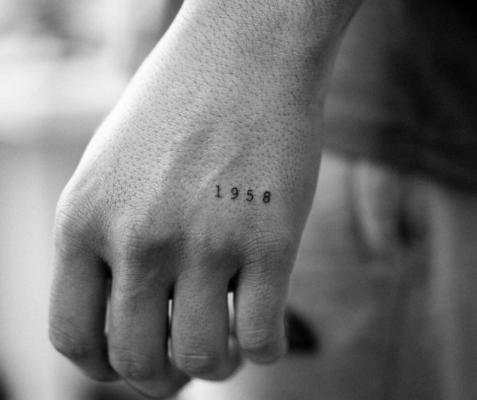 Tatuaje minimalista de fecha en la mano