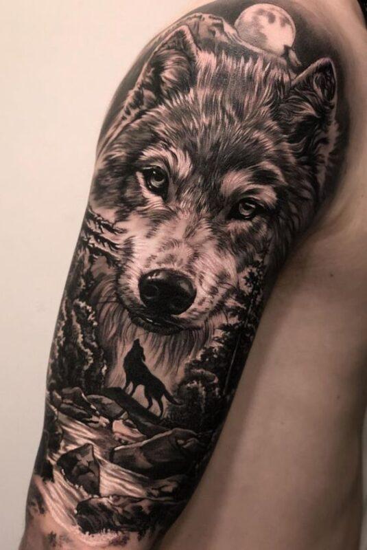 tatuaje de lobo con paisaje en hombro
